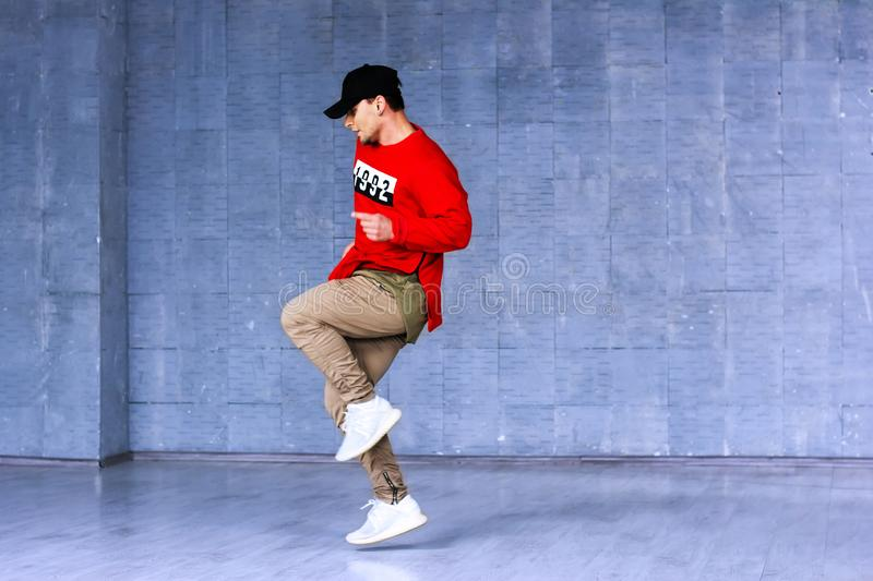 Talented young rapper in movement. Fashion style young boy dancing rap on beton wall background. Hip-hop street perfomance stock photography