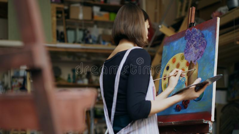 Talented young woman artist painting picture on canvas in art-class. Talented young woman artist painting picture on canvas in art studio indoors stock photography