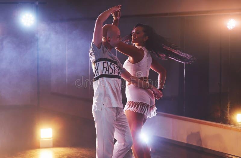 Talentierte Tänzer, die in der Dunkelkammer unter dem Konzertlicht und -rauche durchführen Sinnliche Paare, die ein künstlerische lizenzfreies stockbild