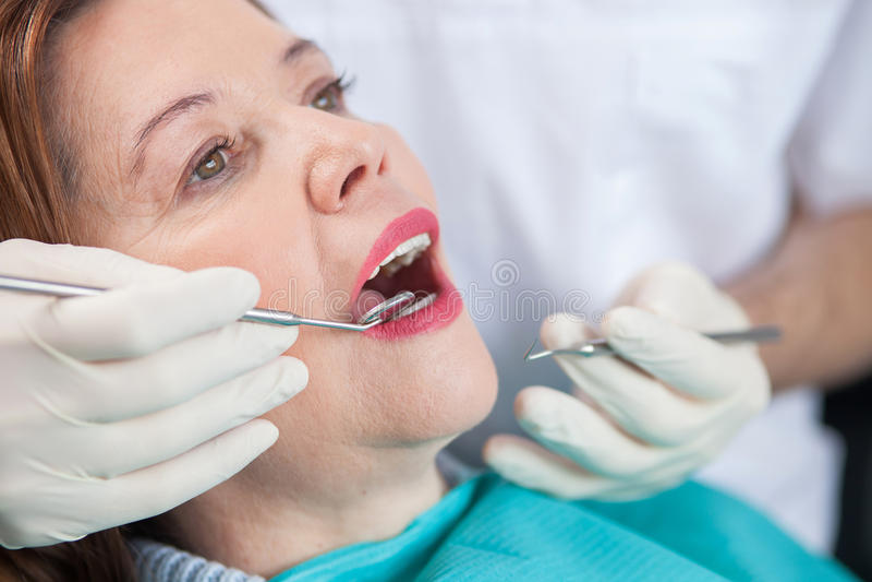 Talentierter männlicher zahnmedizinischer Doktor arbeitet mit Patienten stockfotos