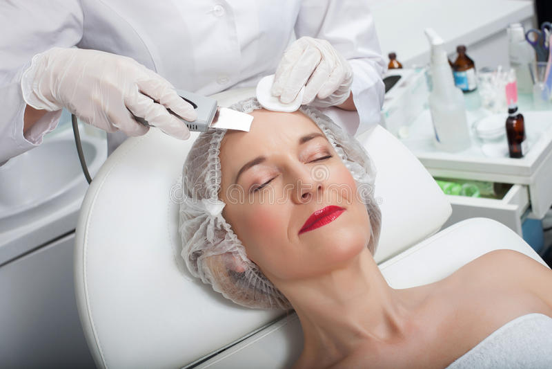 Talentierter weiblicher Kosmetiker unterzieht sich Laser-Behandlung stockfotografie