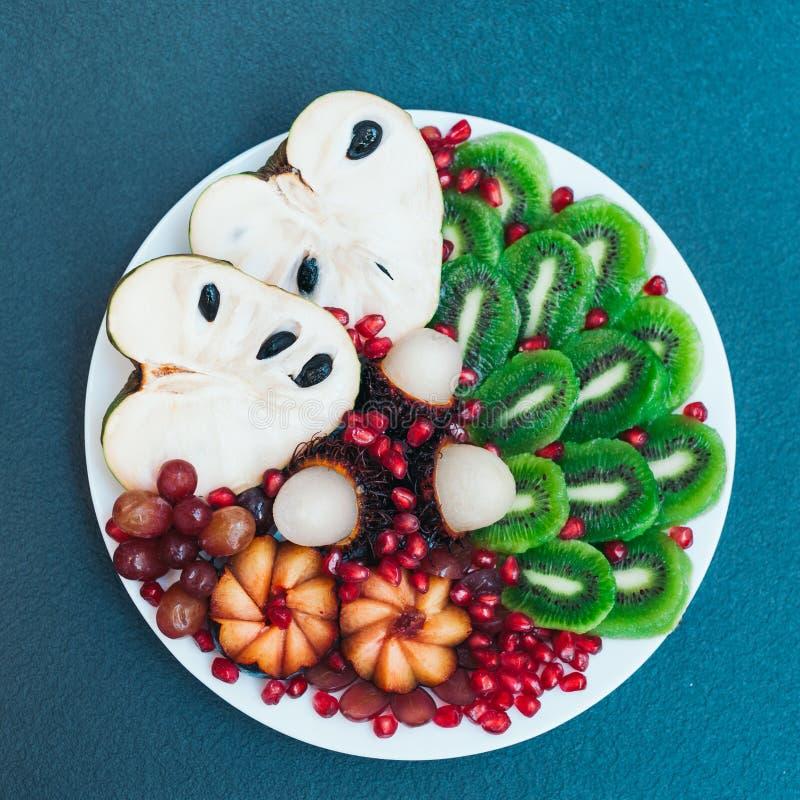 Talerz ?wie?y kiwi, pomergranate, cherimoya, winogrona i bli?niarka odizolowywaj?cy nad b??kitnym t?em, egzotyczne owoce Sztuki j zdjęcie royalty free