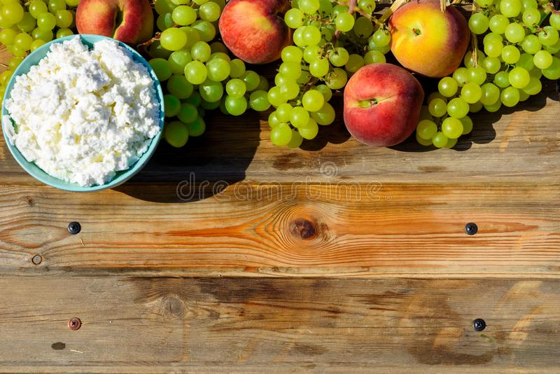 Talerz domowej roboty cha?upa ser, winogrona i brzoskwinia na drewnianym wie?niaka stole, zdjęcia stock