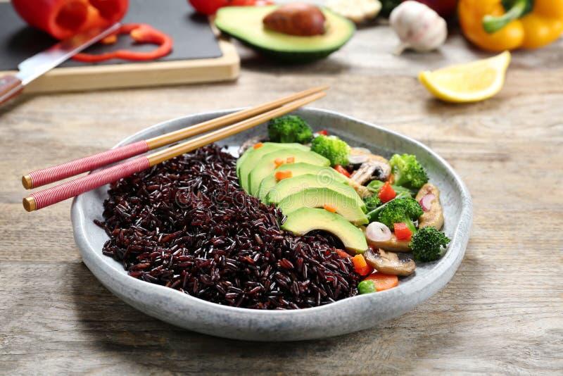 Talerz gotujący brązów ryż z avocado i chopsticks fotografia royalty free