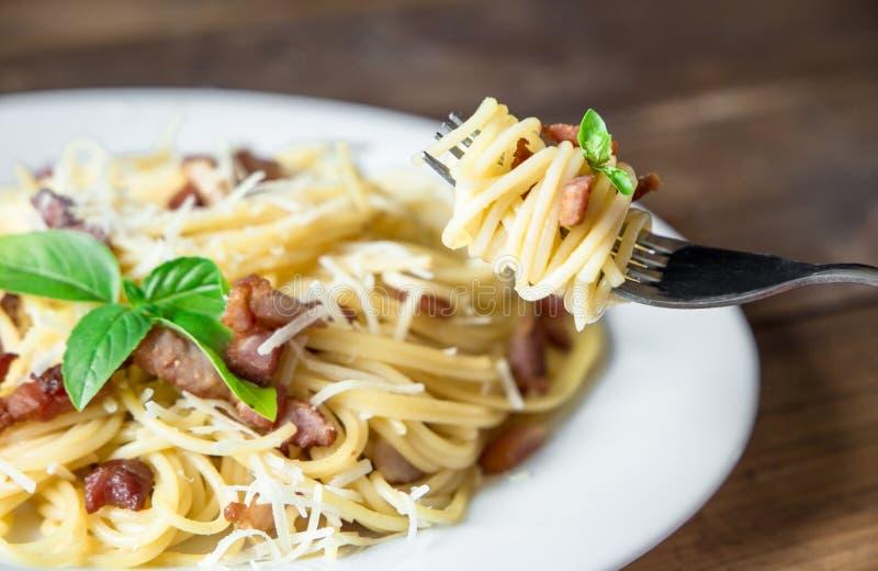 Talerz makaron Carbonara i spaghetti z serem na rozwidleniu na starym drewnianym stole bekonu i parmesan obraz royalty free