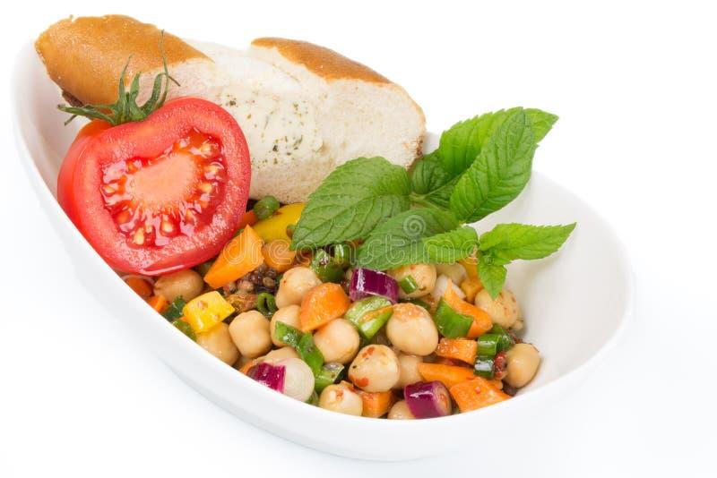 Talerz mieszana sałatka z pokrojonym pomidorem i kawałkiem chleb, zdjęcia royalty free