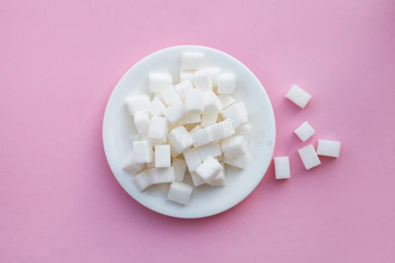 talerz pełno cukrowi sześciany na różowym tle, ryzyko cukrzyce, płaski układ, odgórny widok zdjęcia stock