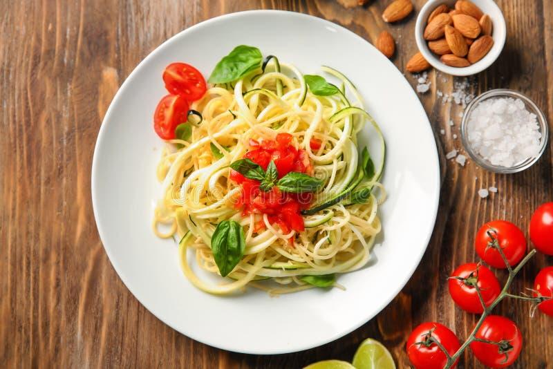 Talerz spaghetti z zucchini i pomidorami na drewnianym stole fotografia royalty free