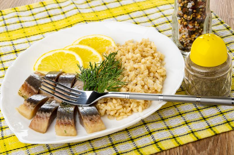 Talerz z śledziem, ryż, cytryną i koperem, rozwidlenie, condiment, pieprz na pielusze na stole zdjęcia stock
