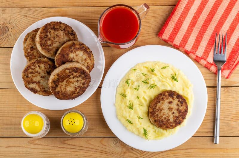 Talerz z cutlets, pomidorowym sokiem, talerzem z, solą i pieprzem, smażącym puree ziemniaczane i cutlet, rozwidlenie na pielusze  zdjęcie stock
