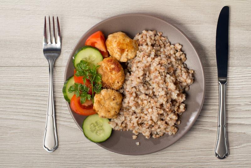 Talerz z gryką, smażącymi mięsnymi cutlets i kawałkami świeży cuc, zdjęcia stock