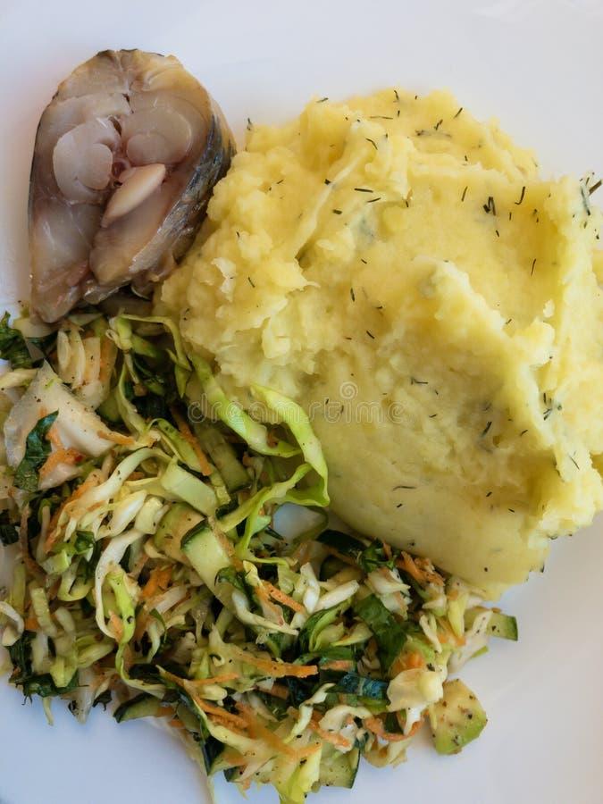Talerz z kawałkiem śledź, kartoflana breja, kapuściana sałatka mieszająca z marchewkami i dandelion liście, obrazy stock