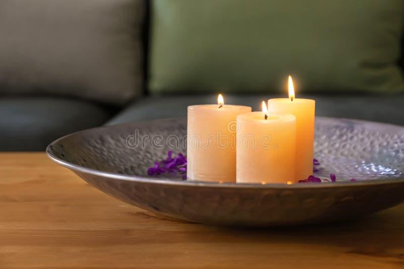 Talerz z palenie wosku świeczkami, wodą i kwiatów płatkami na drewnianym stole, fotografia stock