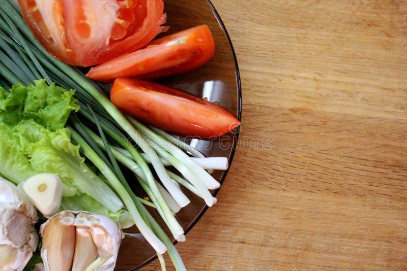 Talerz z pomidorem, czosnkiem i ziele na drewnianej deski tle, zdjęcia stock