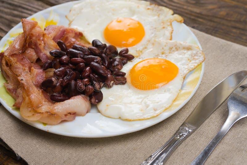 Talerz z rozdrapanymi jajkami, bekonem i fasolami na drewnianym wieśniaka stole, fotografia royalty free