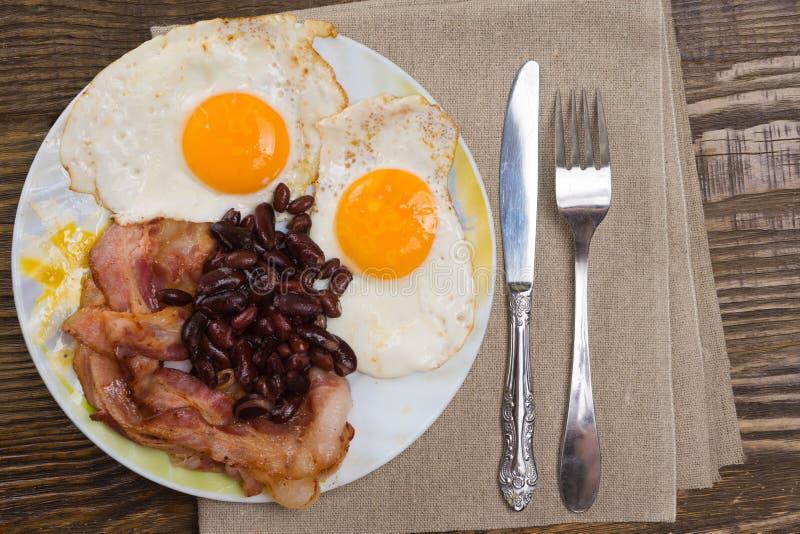 Talerz z rozdrapanymi jajkami, bekonem i fasolami na drewnianym wieśniaka stole, obrazy stock