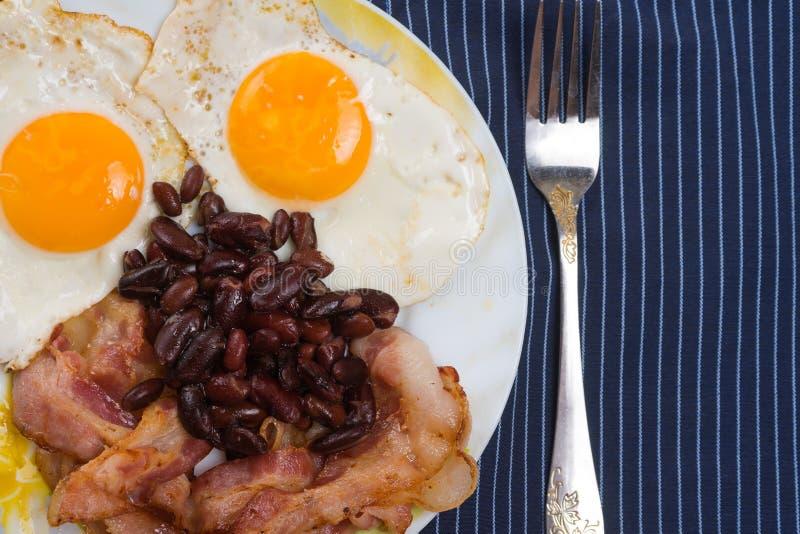 Talerz z rozdrapanymi jajkami, bekonem i fasolami na drewnianym wieśniaka stole, zdjęcia stock