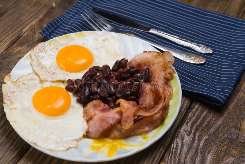 Talerz z rozdrapanymi jajkami, bekonem i fasolami na drewnianym wieśniaka stole, obraz stock