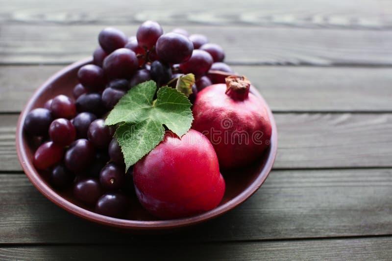 Talerz z słodkimi winogronami i granatowami na drewnianym stole obraz stock