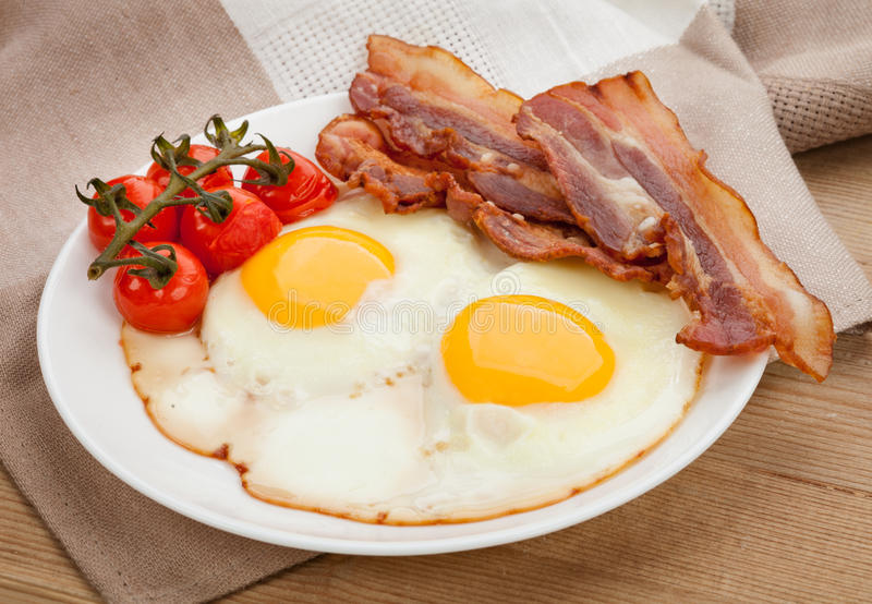 Talerz z smażącymi jajkami, bekon na pokładzie obraz royalty free