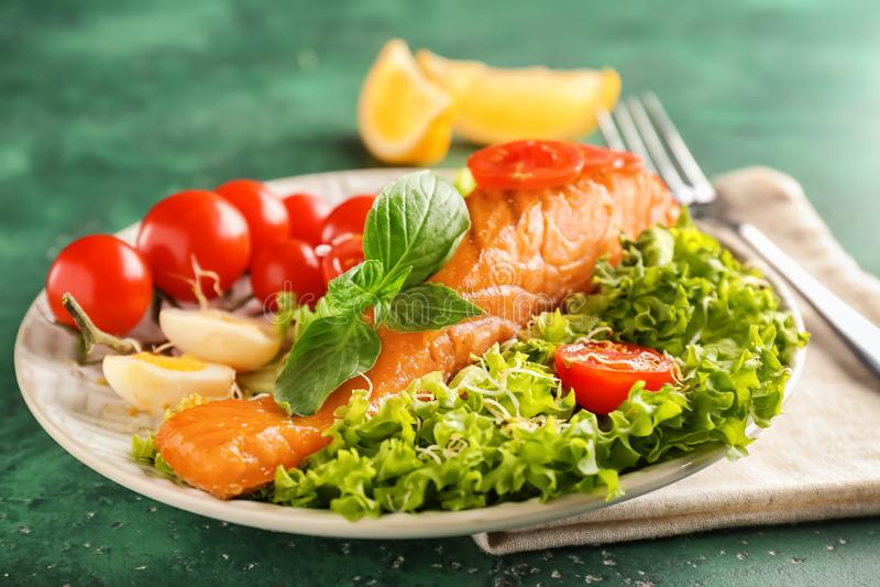 Talerz z smakowitą łososia i warzywa sałatką na koloru stole fotografia royalty free
