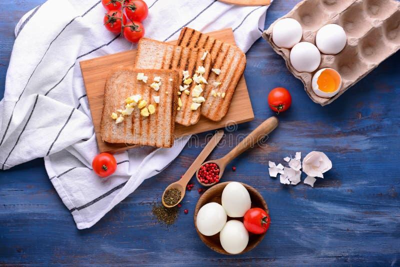 Talerz z smakowitymi gotowanymi jajkami i wznoszącym toast chlebem z pikantność na koloru drewnianym stole zdjęcie stock