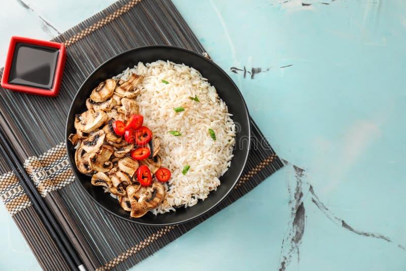Talerz z smakowitymi gotowanymi ryż, pieczarkami i warzywami na światło stole, zdjęcie royalty free