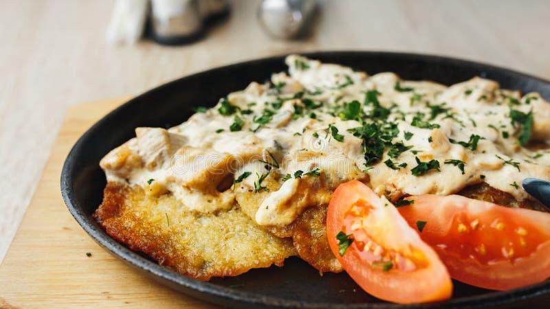 Talerz z smakowitymi kartoflanymi blinami z pomidorami i sosem na drewnianym stole zdjęcia royalty free
