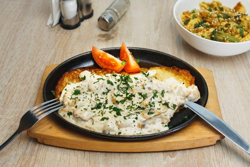 Talerz z smakowitymi kartoflanymi blinami z pomidorami i sosem na drewnianym stole obrazy stock