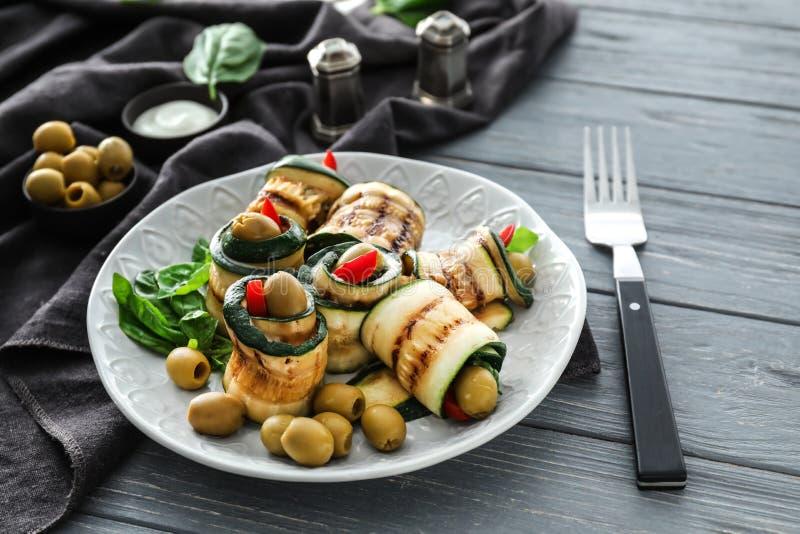 Talerz z smakowitymi zucchini rolkami i zielonymi oliwkami na drewnianym stole fotografia royalty free