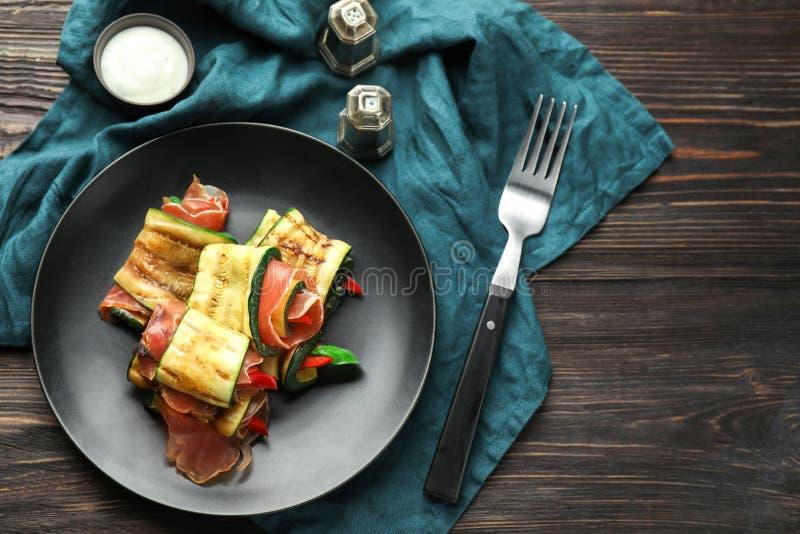 Talerz z smakowitymi zucchini rolkami na drewnianym stole obraz royalty free
