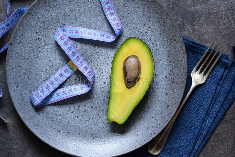 Talerz z taśmy miarą, rozwidleniem i avocado na ciemnym tle z miejscem dla teksta, ?ywienioniowy od?ywianie obraz royalty free
