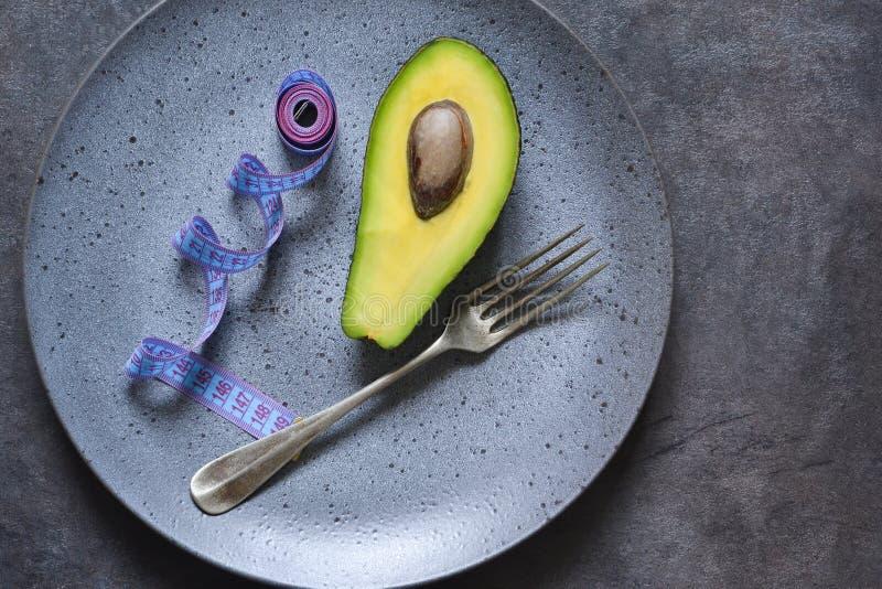 Talerz z taśmy miarą, rozwidleniem i avocado na ciemnym tle z miejscem dla teksta, zdjęcie stock