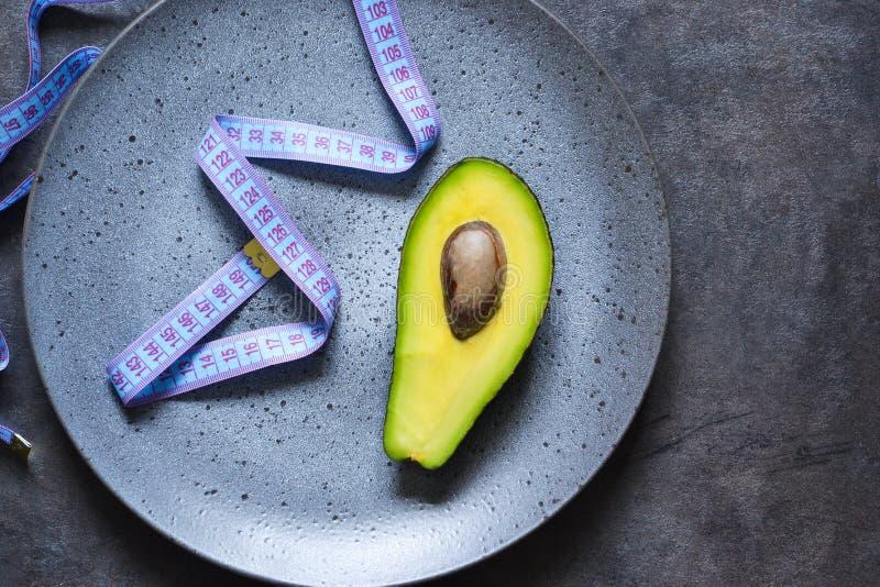 Talerz z taśmy miarą, rozwidleniem i avocado na ciemnym tle z miejscem dla teksta, obraz stock