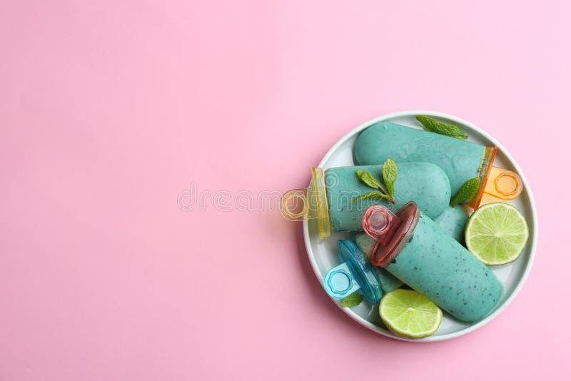 Talerz z wyśmienicie spirulina popsicles i wapno na koloru tle, odgórny widok zdjęcia royalty free