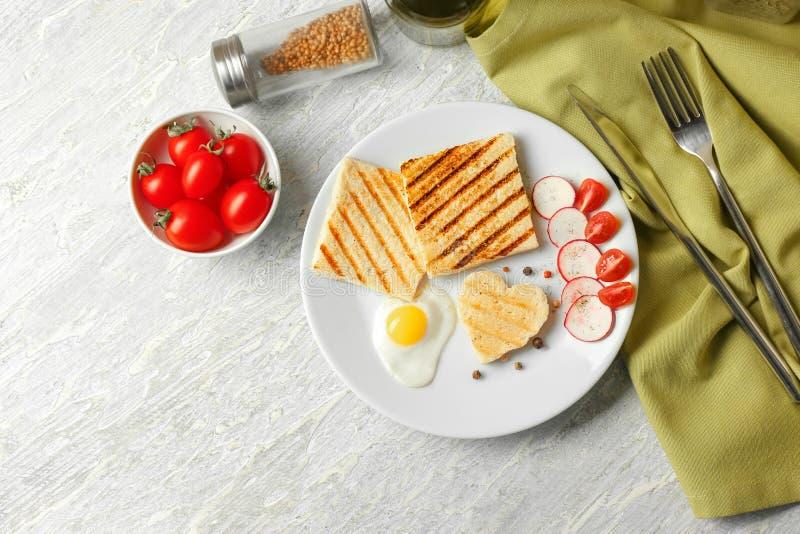 Talerz z wznoszącym toast chlebem, smażącym jajkiem i warzywami na stole, obraz stock