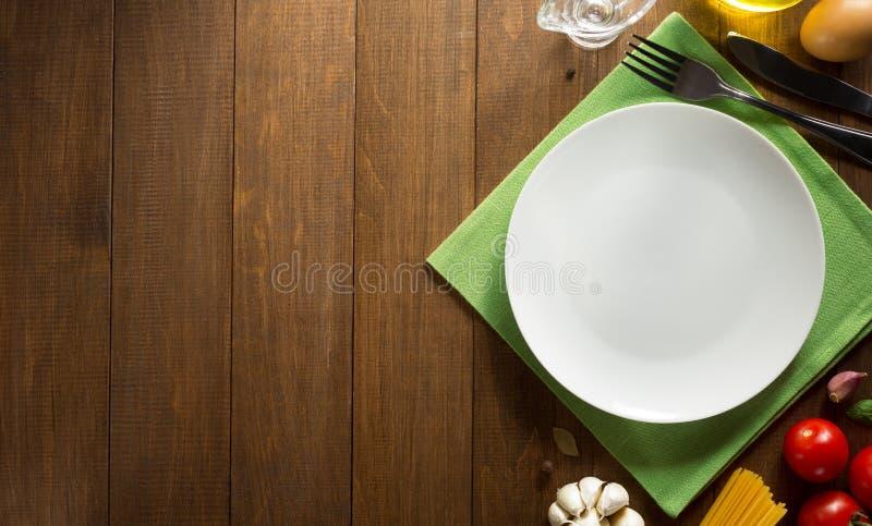 Talerza i ziele składniki przy drewnem obraz stock