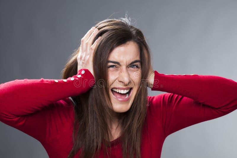 30-talflicka som får tokig och att lida från migrän som täcker henne öron med hennes händer royaltyfria foton