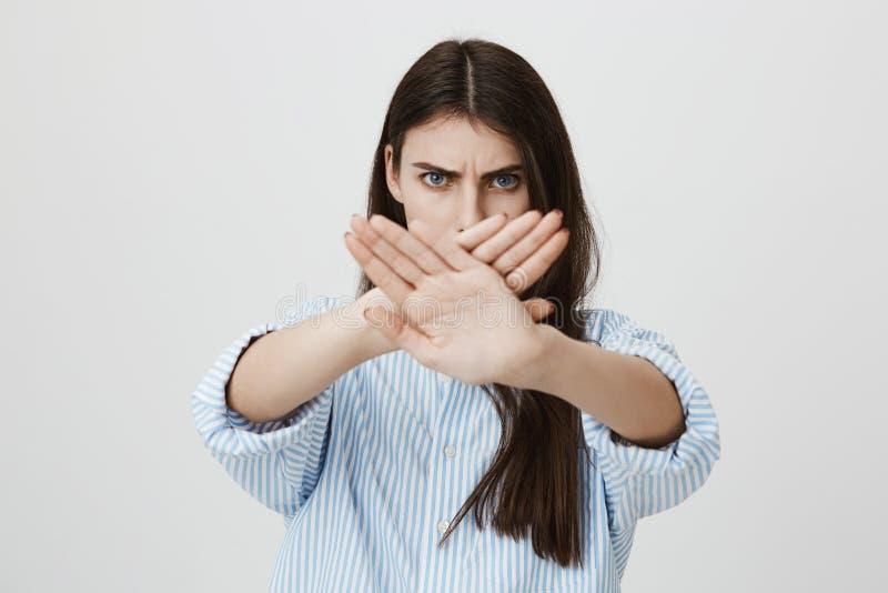 Talia portret niespokojny, poważny brunetek ręk w skrzyżowanie i dosyć, patrzeje gniewny przy kamerą zdjęcie royalty free