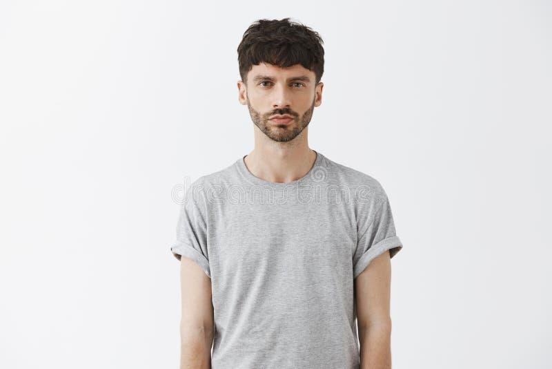 Talia strzał przyglądający unemotional atrakcyjny dorosły mężczyzna patrzeje kamera spokój w szarej koszulce i surowy fotografia stock