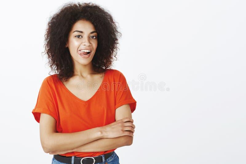 Talia strzelająca flirty otwarta atrakcyjna kobieta z afro fryzurą wtyka out jęzor, trzymający ręki krzyżować, i zdjęcia royalty free