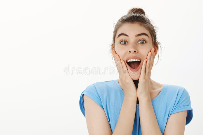 Talia strzelająca z podnieceniem szczęśliwa i śliczna kobieta z babeczki fryzurą, ono uśmiecha się szeroko i ono wpatruje się z s fotografia royalty free