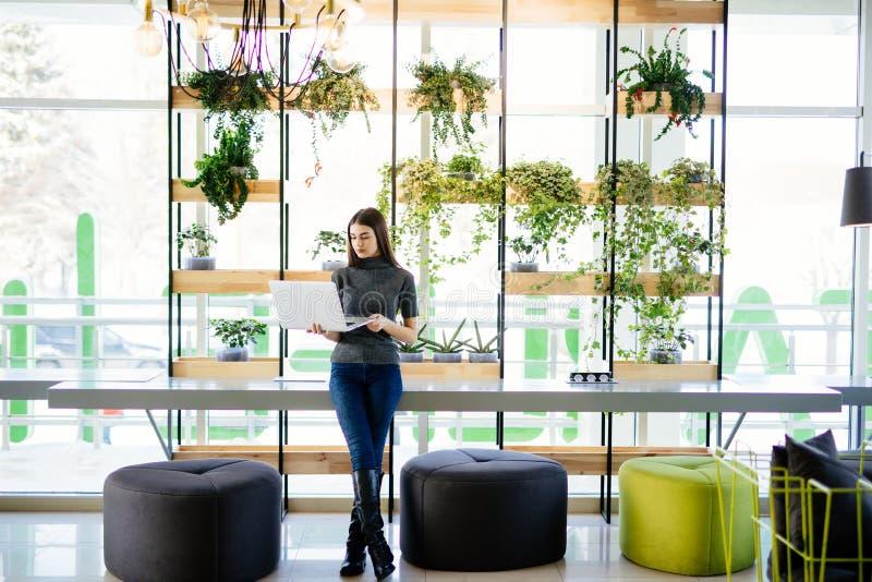 Talia w górę portreta poważny młody bizneswomanu mienia laptop podczas gdy pojęcia nowożytny biuro obrazy royalty free