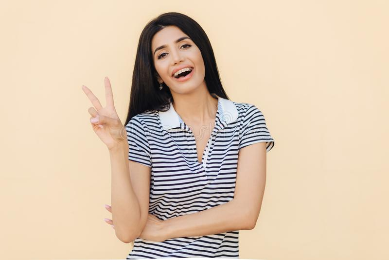 Talia w górę portreta szczęśliwej brunetki młoda kobieta pokazuje pokoju znaka, ono uśmiecha się szczęśliwie przy kamerą, jest ub fotografia stock