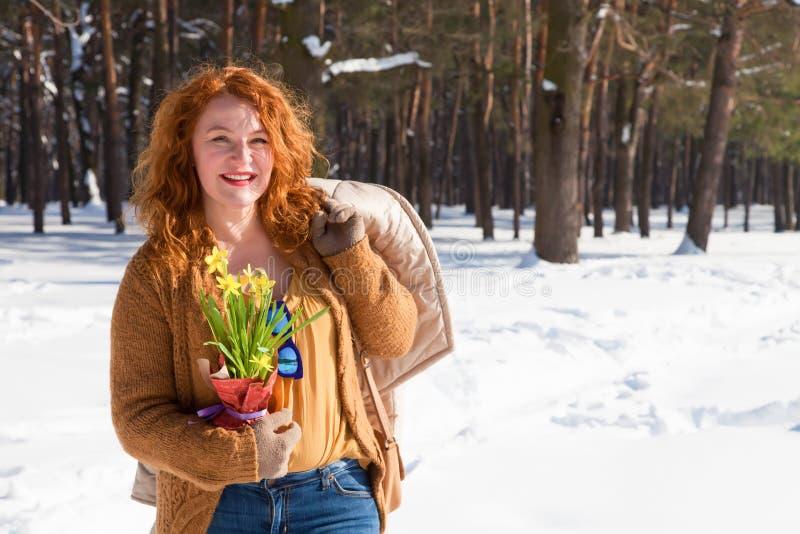 Talia w górę z podnieceniem czerwonej z włosami kobiety utrzymuje jej żakiet nad ramieniem podczas gdy mieć spacer przez zima las zdjęcia stock