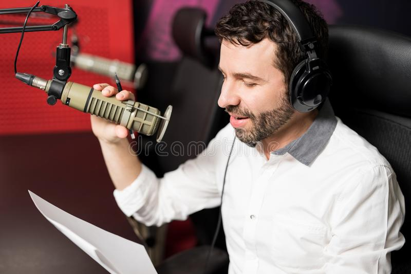 Talk show radio host talking into microphone. Close up good looking male radio host broadcasting through microphone in studio royalty free stock photo