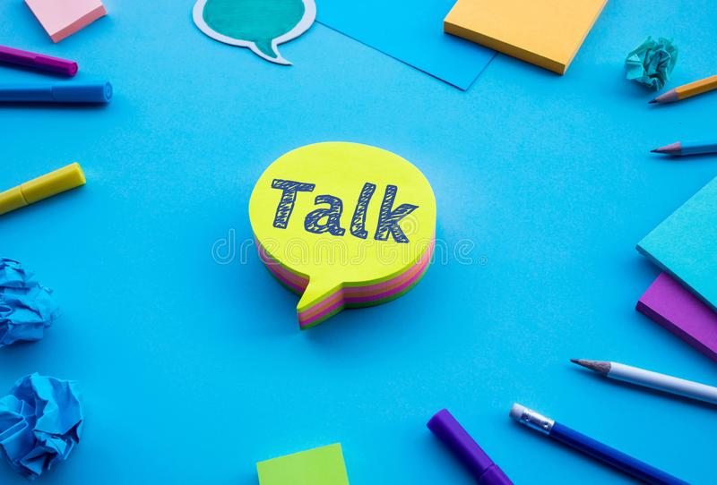 Talk text on chat,speech bubble on blue desk table color background.social media and online marketing concepts. Ideas stock photos