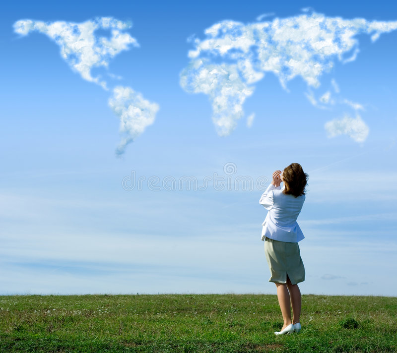 Talk to the world. Woman talking to the world. Shouting loud on a green field, the clouds on the sky form the world map