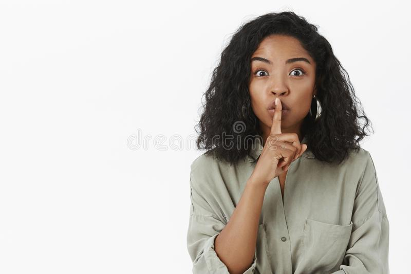 Talkative attractive african american woman in trendy shirt with curly hairstyle spreading gossip asking friend keep. Secret saying shh keeping voice down stock image