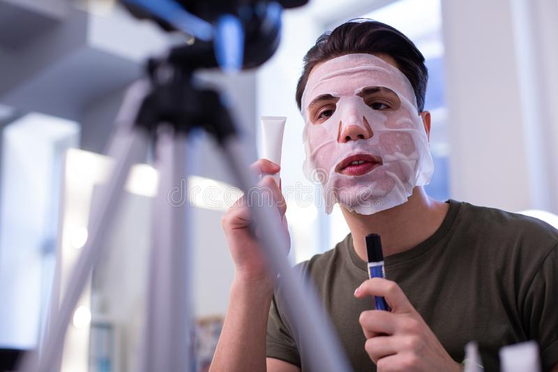 Talkative good-looking young man in nourishing face mask. Tubes with products. Talkative good-looking young man in nourishing face mask and holding containers stock photography